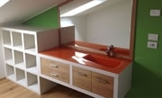 Inverso washbasin, shiny finish, orange, installed upon a custom-made piece of furniture.